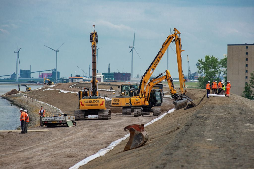 Three excavators pile up dirt to raise the level of a sea dike near Defzijl, Netherlands.