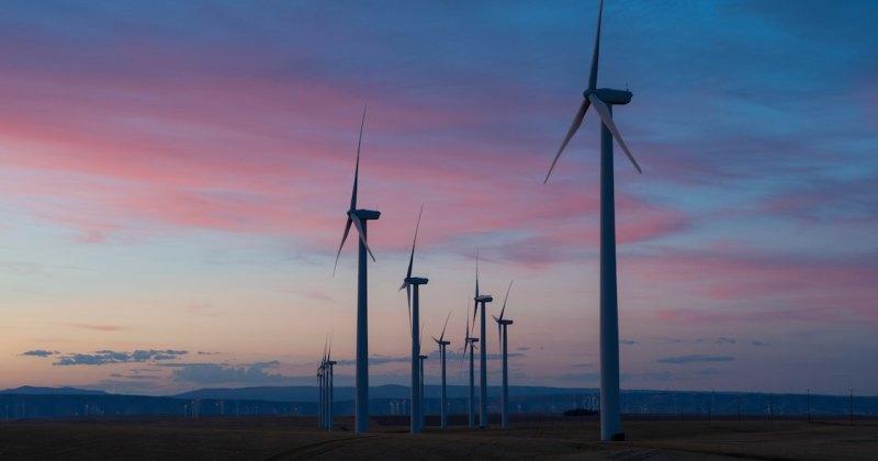 White wind mills against a sunset in the Oregon desert.