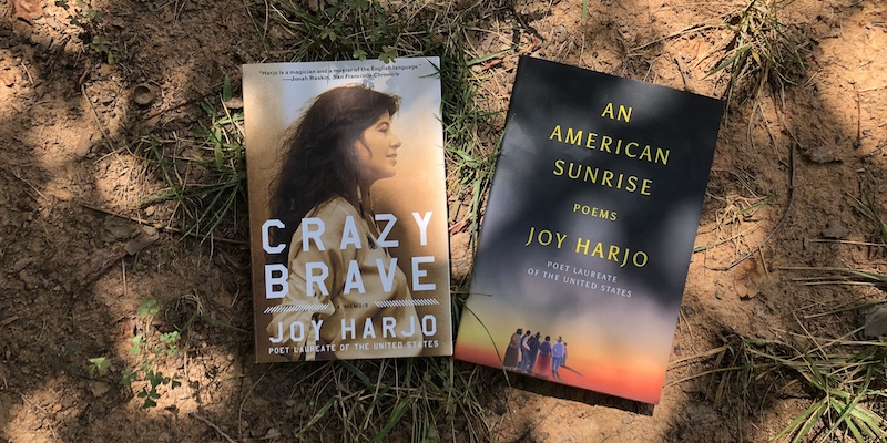 A photo of Crazy Brave and An American Sunrise by Joy Harjo in the dirt.