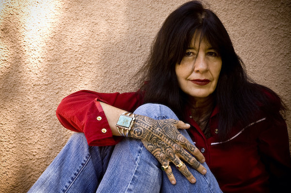 A photo of Joy Harjo wearing a red shirt and blue jeans.