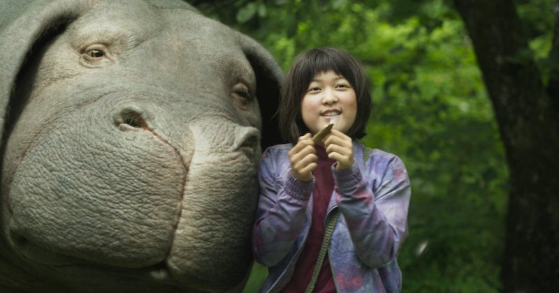 Mija stands next to Okja in a screenshot from the film Okja.