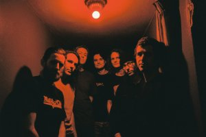 A photo of the band members of King Gizzard & The Lizard Wizard under a red light.