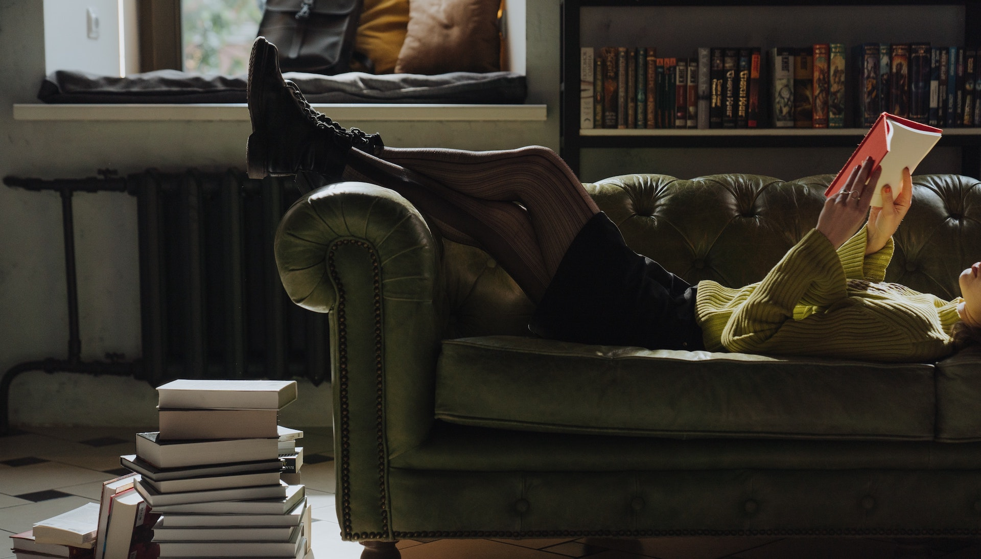 A woman reclines on a sofa reading a book.