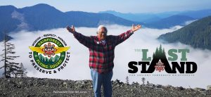 A photo of Pacheedaht Elder Bill Jones standing in front of a mountain valley with visible deforestation in the background.