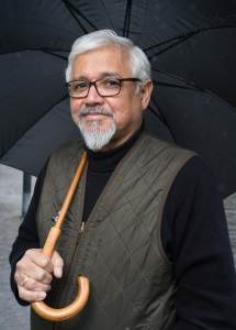 A photo of author Amitav Ghosh looking into the camera while holding an umbrella.